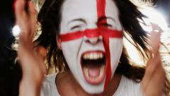 Female soccer fan with England flag on the face screaming into a camera - stock footage