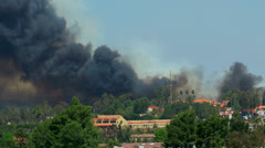 Smoke from large fire behind homes. - stock footage