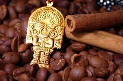 Closeup of coffee beans with golden Indian god Stock Photos
