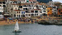 Sailing in front of a Mediterranean fishing village. Small boat sailing Stock Footage