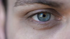 intense gaze: blue eye in macro 4k footage of young handsome man - stock footage