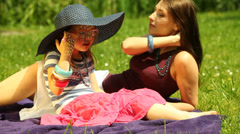 Mother with little daughter relaxing on the meadow. Stock Footage