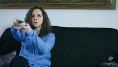 Funny clip of woman trying change tv channel: sitting, sofa, remote control, 4k Stock Footage