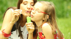 Mother with little daughter blowing a soap bubbles outdoor Stock Footage