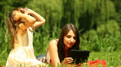 Mother using tablet when daughter putting on glasses and sunglasses. Outdoor. Stock Footage