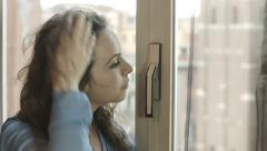 Lonely thoughtful woman at the window: problem, pensive, sad. 4k footage Stock Footage