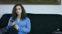 Funny clip of woman trying to change tv channel: sitting, sofa, remote control Stock Footage