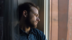 Portrait of handsome young sad man in front of a window Stock Footage