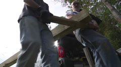 Stock Video Footage of walking trails men carry timbers for connector bridge completed