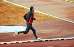 adult man running on athletics track - stock photo
