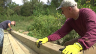 Stock Video Footage of walking trails men set timbers for connector bridge