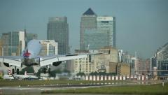 Jet Airliner Lands At City Airport - Skyscraper Back Drop Stock Footage