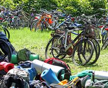 parked bicycles and many backpacks on the lawn during a stop in the countrysi - stock photo