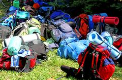 colorful pile of backpack of scouts during an excursion in the nature park - stock photo