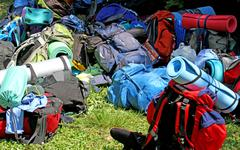 colorful pile of knapsacks of scouts during an excursion in the park - stock photo