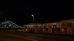 NIGHT TRAMS IN FRONT OF LIBERTY BRIGDE - stock footage