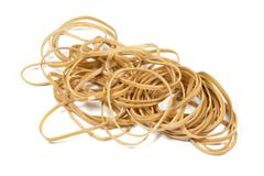 beige elastic bands stacked in a pile - stock photo