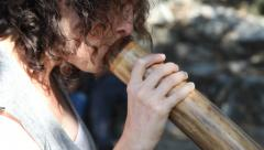 A female plays the didjeridoo, an aboriginal, indigenous  wind instrument - stock footage