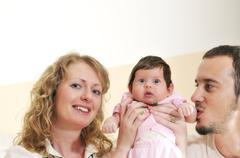 Stock Photo of indoor portrait with happy young family and  cute little babby