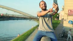 Man taking selfie photo with cellphone, sitting on the wall by the river HD Stock Footage