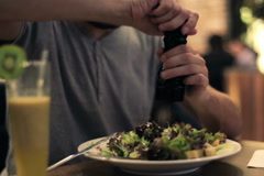 Man spicing up salad with salt and pepper in restaurant NTSC Stock Footage