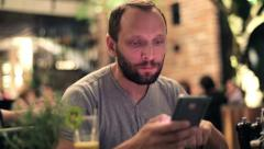Young man with smartphone eating tasty salad in restaurant HD Stock Footage