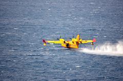Airplane on sea taking water - stock photo