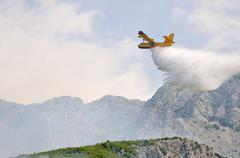 Airplane droping water on fire - stock photo