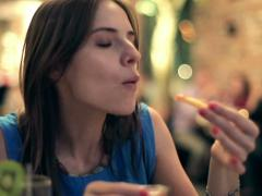 Stock Video Footage of Young woman eating french fries in restaurant NTSC