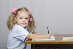 little girl sitting at table and wrote in notebook - stock photo