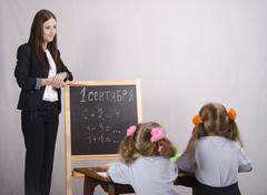 girl teacher teaches two disciples - stock photo