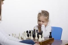 girl playing chess in a good mood - stock photo