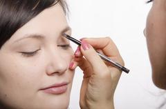 makeup artist brings eyebrow pencil model - stock photo