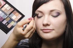 Makeup artist colors upper eyelids model Stock Photos