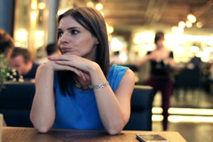 Young pensive woman sitting alone in restaurant NTSC Stock Footage