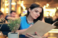 Stock Video Footage of Young woman reading menu in restaurant NTSC