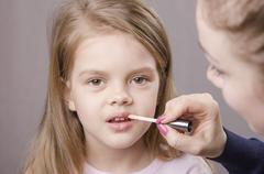 Makeup artist deals shine on the lips girls Stock Photos
