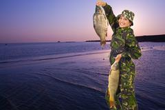 Happy fisherwoman holding big carps - stock photo