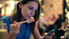 Woman texting on smartphone and eating salad in restaurant HD Stock Footage
