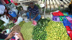 Local man sitting and selling limes and lemons at Hikkaduwa market. Stock Footage