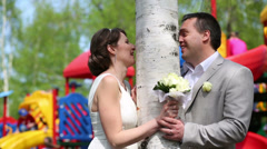 Newly married couple standing near birch against playground Stock Footage