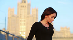 Young woman correct hair and smiling against skyscraper Stock Footage
