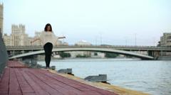 woman walk line on tiptoe along wooden waterfront near railings - stock footage