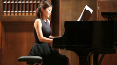 Graceful woman pianist sits at the piano in concert stage - stock footage