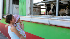 Girl on mothers arms look at cows in stall windows. Stock Footage