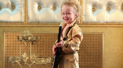 Little boy in pop retro costume with guitar toy at studio Stock Footage