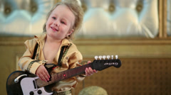 Boy in pop retro costume have fun with guitar toy at studio Stock Footage