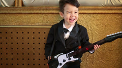 Little boy in black tuxedo playing guitar toy at studio Stock Footage