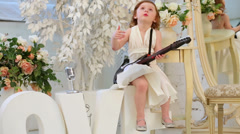 Beautiful little girl in white dress sings and plays guitar Stock Footage
