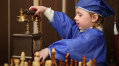 Little girl  in blue suits of graduates with old phone and chess Stock Footage